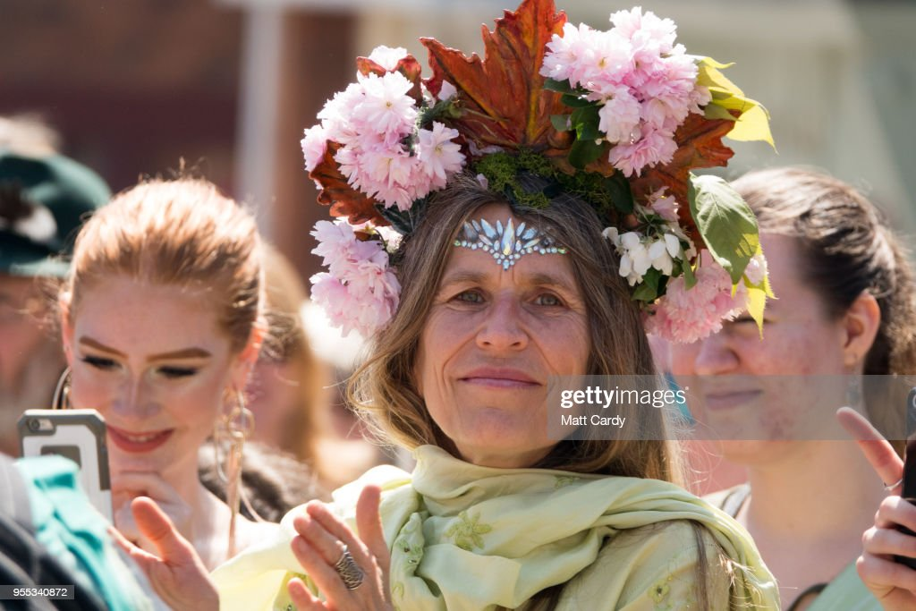A woman applauds as the Pentacle Drummers perform as they wait for the Glastonbury Dragons to be paraded through the town as they take part in May Fayre and Dragon Procession in Glastonbury on May 6, 2018 in Somerset, England. To celebrate the arrival of summer, the Glastonbury Dragons, alongside Gwythyr Ap Greidal, the Summer King and the Winter King, Gwyn Ap Nudd, were paraded through the town to the lower slopes of Glastonbury Tor where the event was marked with a Beltane themed ceremony.