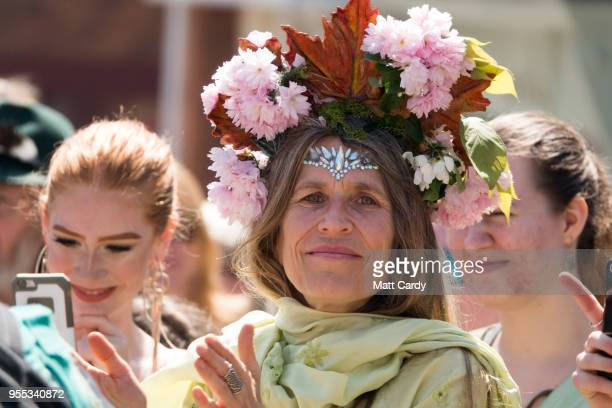 A woman applauds as the Pentacle Drummers perform as they wait for the Glastonbury Dragons to be paraded through the town as they take part in May...