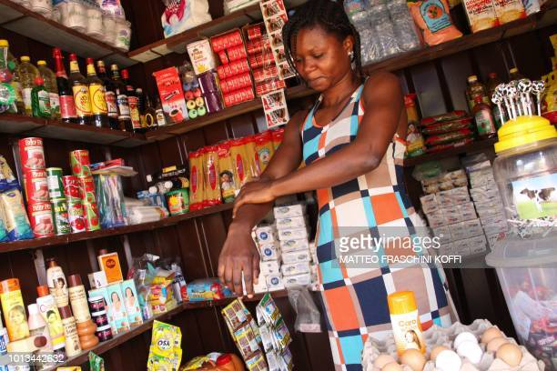 A woman applies a cream called Caro White Lightening Beauty Cream at her shop in Lome on June 27 2018 Africa is experiencing a massive trend of skin...