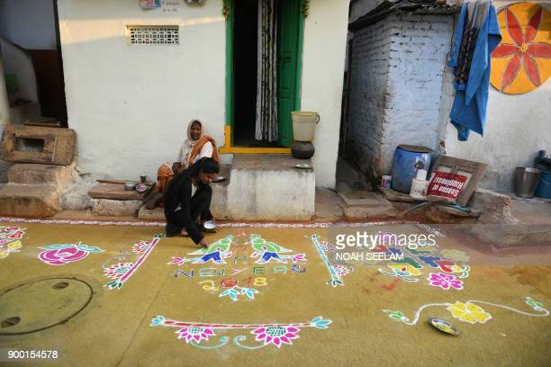 A woman applies coloured powder to a 'rangoli' a Hindu ritual design to usher in the New Year in front of a home in Hyderabad on January 1 2018...