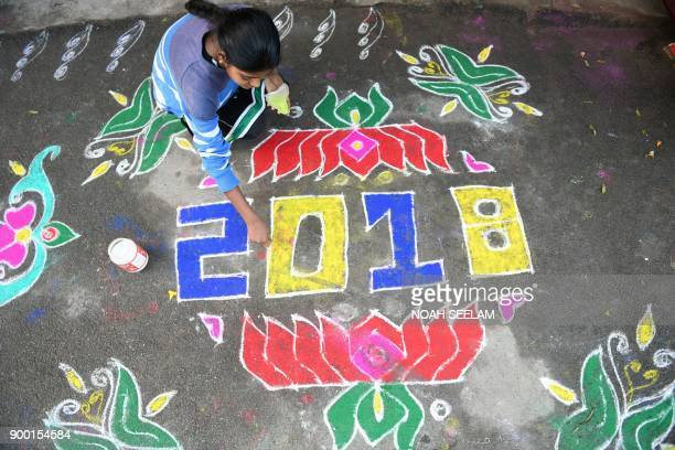 TOPSHOT A woman applies coloured powder to a 'rangoli' a Hindu ritual design to usher in the New Year in front of a home in Hyderabad on January 1...