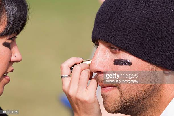 woman applies eye black grease under man eyes - football body paint stock photos and pictures