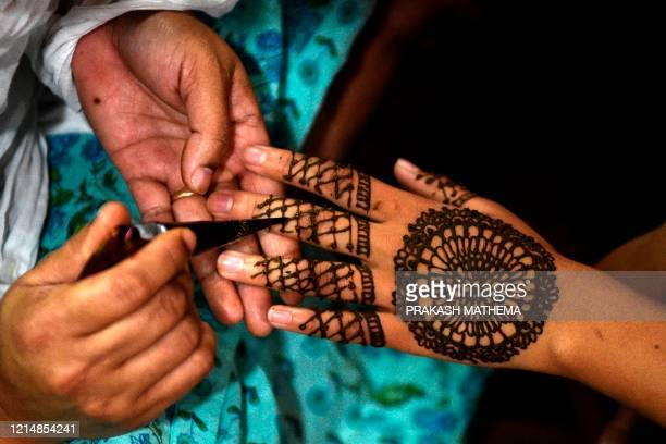 A woman applies hennas on the hand during 'Chand Raat' or 'Night of the Moon' in Kathmandu on May 24 on the eve of Eid alFitr festival Muslims around...