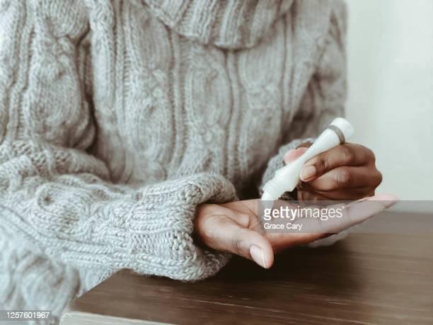 woman applies lotion to hands - handcrème stockfoto's en -beelden