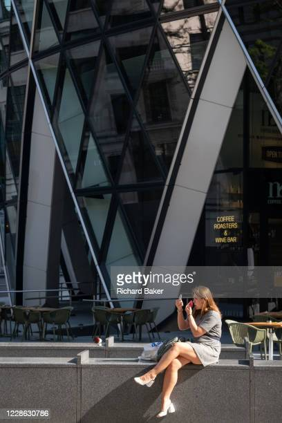 A woman applies makeup beneath the architecture of the Swiss re Building aka the Gherkin in the City of London during the Coronavirus pandemic a time...