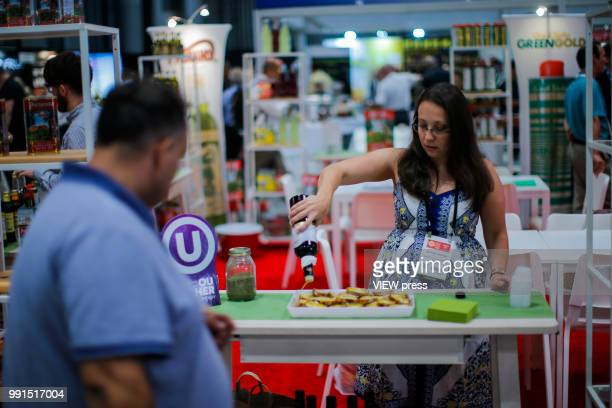 A woman applies olive oil on bread during The Summer Fancy Food Show at the Javits Center in the borough of Manhattan on July 02 2018 in New York The...