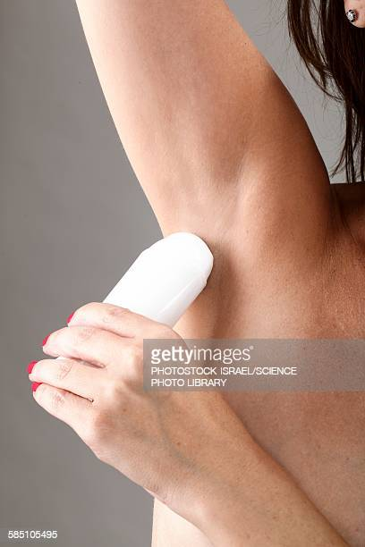 Woman applies underarm deodorant