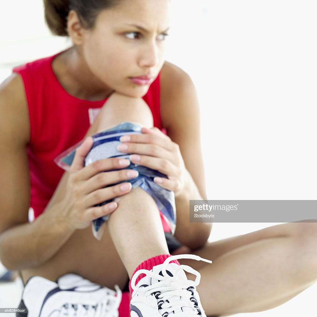 woman applying a cold pack to her leg : Stock Photo