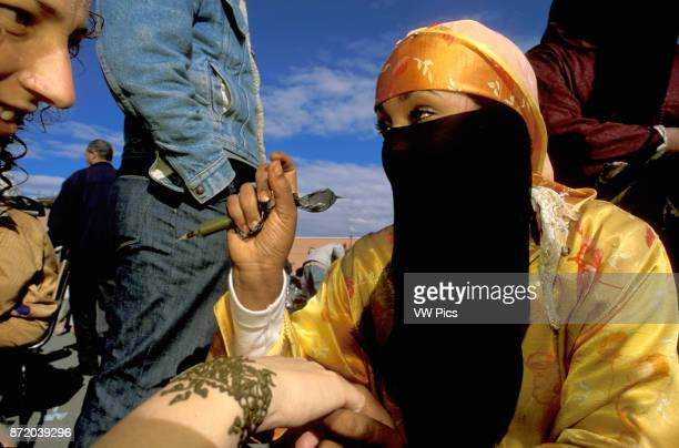 Woman applying a henna tattoo on a tourists hand in the Djemaa elFna market in Marrakech Morocco
