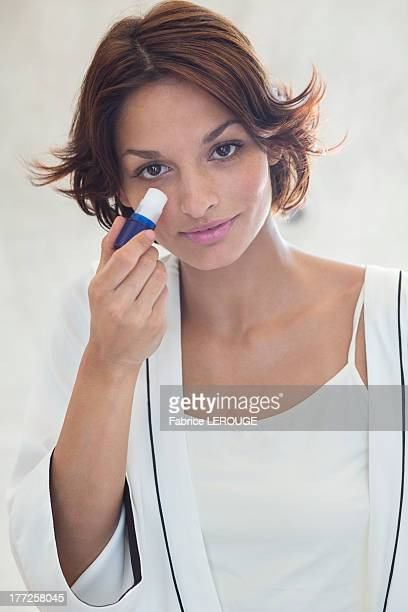Woman applying anti wrinkle on her face