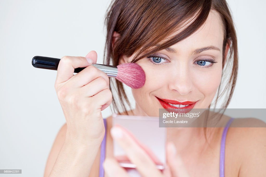 Woman applying blush in front of mirror : Stock Photo
