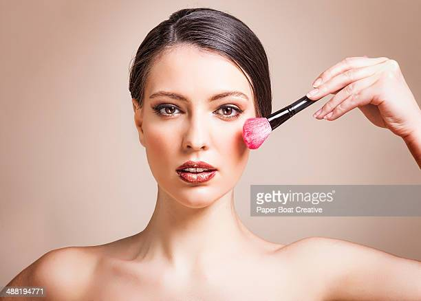 Woman applying blush on to her cheeks