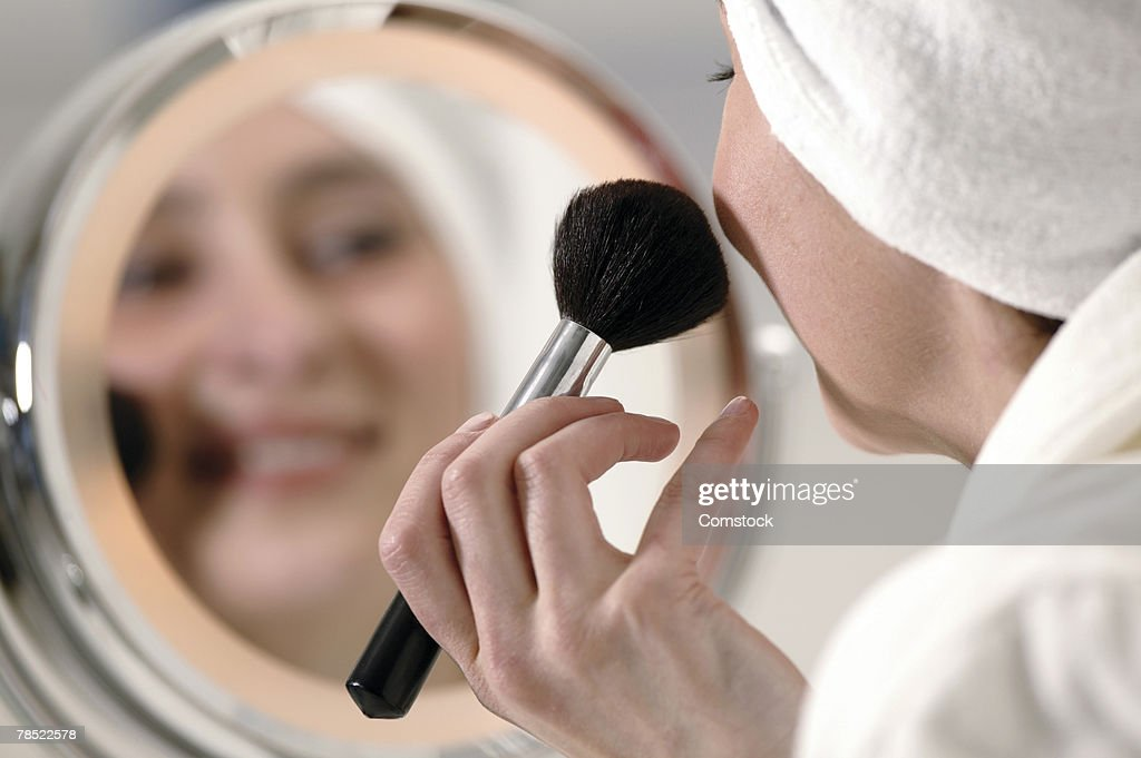 Woman applying blush : Stock Photo