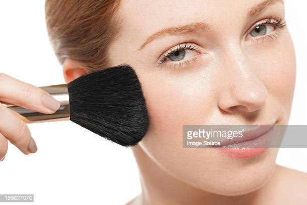 Woman applying blusher with brush
