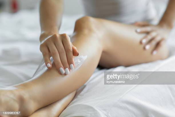 woman applying body lotion on her legs at her bedroom. - the human body stock pictures, royalty-free photos & images