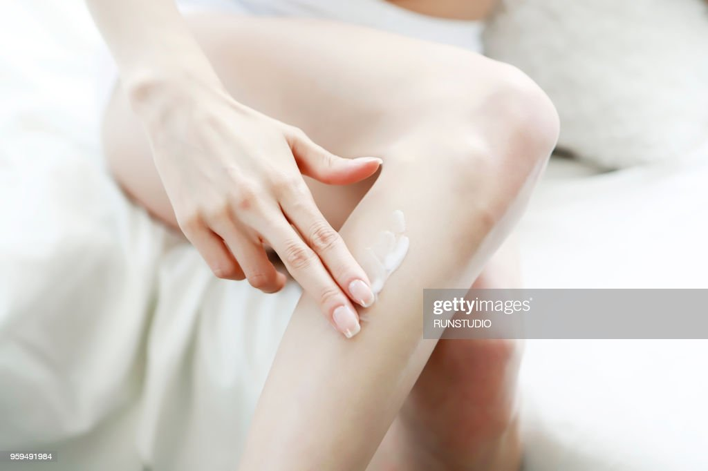 Woman applying body lotion on leg : Stock-Foto