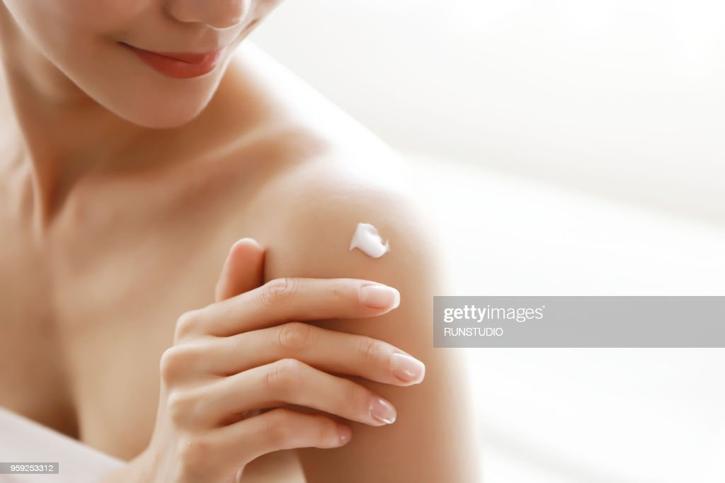 woman applying body lotion on shoulder : Stock-Foto