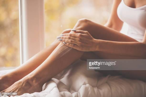 application d'hydratant pour le corps sur ses jambes de femme - massage room photos et images de collection