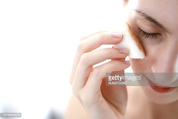 woman applying cleansing lotion to face, using cotton wool pad - padding stock photos and pictures