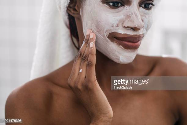 woman applying cosmetic face mask - face mask beauty product stock pictures, royalty-free photos & images