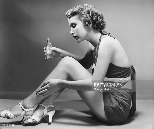 woman applying cosmetic on calf (b&w) - silhueta de corpo feminino preto e branco - fotografias e filmes do acervo