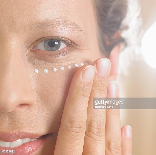 Woman (36y) applying cream on face