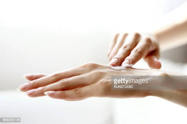 woman applying cream on hand - dedo humano imagens e fotografias de stock