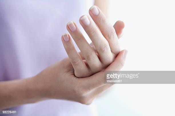 woman applying cream to hands, close-up - eincremen stock-fotos und bilder