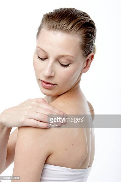 woman applying cream to her shoulder - off shoulder stock pictures, royalty-free photos & images