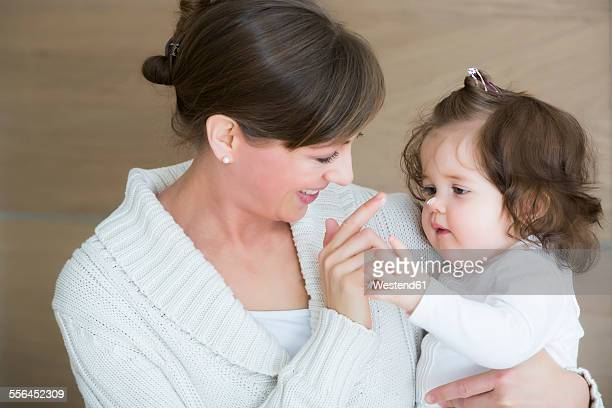 Woman applying creme on daughters nose