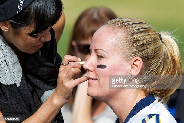 woman applying eye black grease - football body paint stock photos and pictures