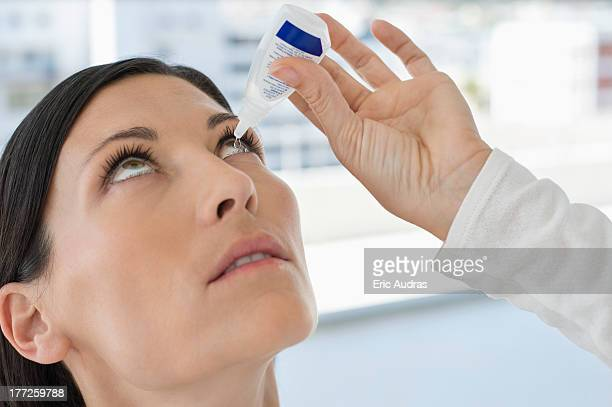 Woman applying eye drops into eye