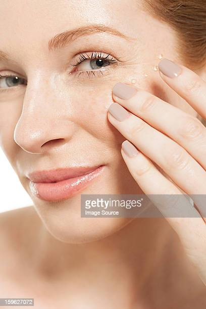 Woman applying eye gel