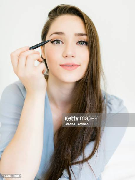 woman applying eyeliner - eye liner stock pictures, royalty-free photos & images