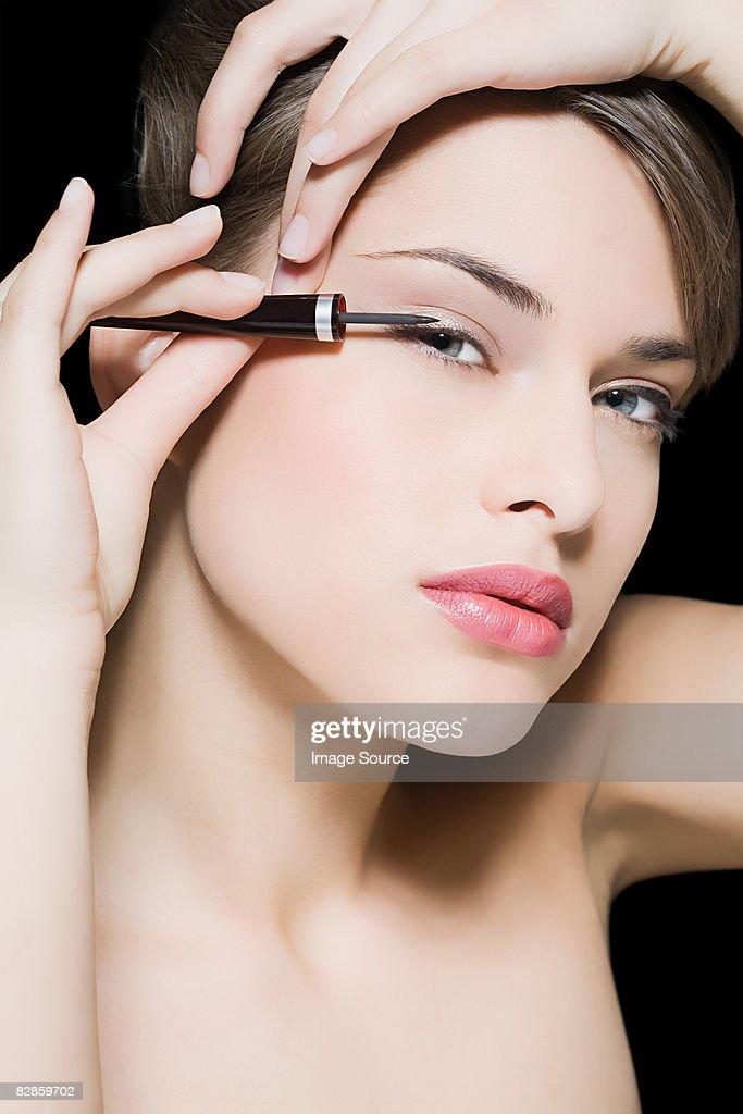 Woman applying eyeliner : Stock Photo