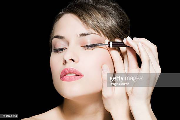 woman applying eyeliner - eye liner stock photos and pictures