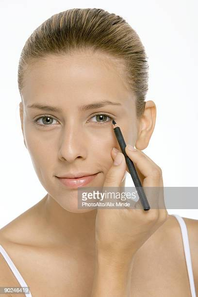 Woman applying eyeliner, smiling at camera, close-up