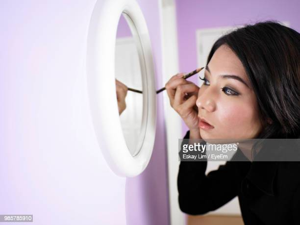 woman applying eyeliner while looking in mirror at home - eye liner stock pictures, royalty-free photos & images
