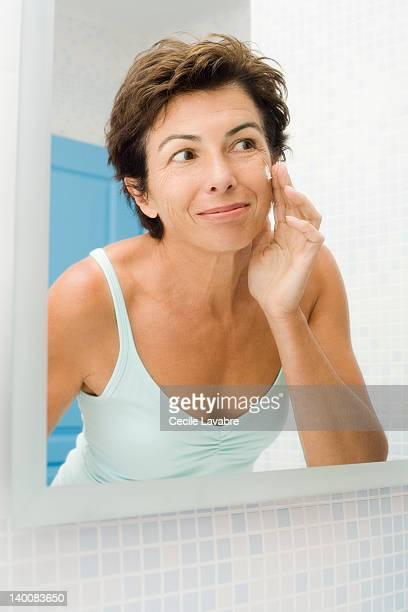 woman applying face cream in front of mirror - decote peito - fotografias e filmes do acervo