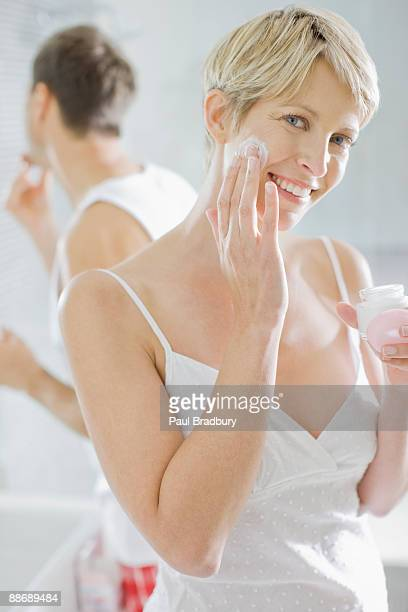 Woman applying face cream in the morning