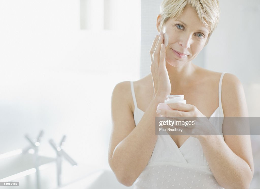 Woman applying face cream in the morning : Stock Photo