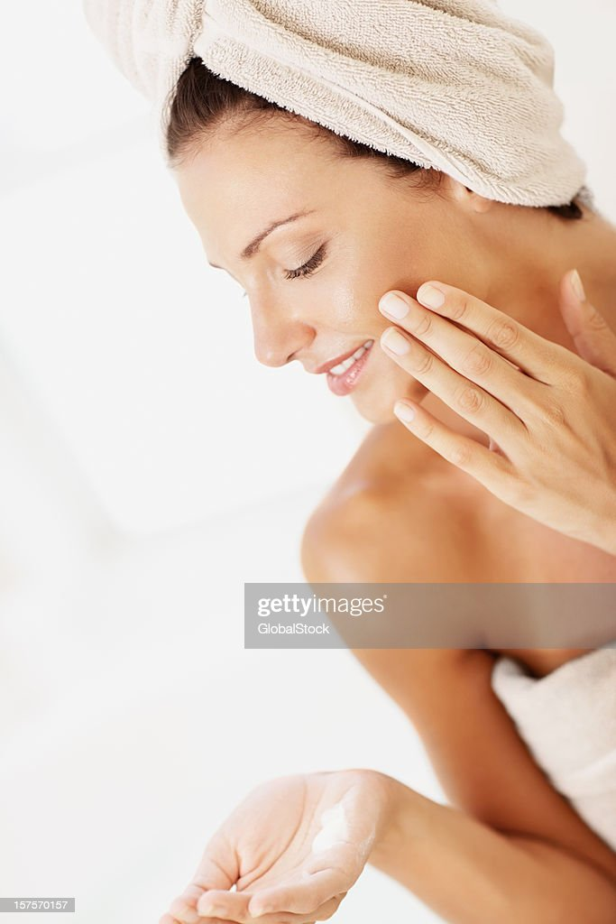 Woman applying face cream in towel after shower : Stock Photo