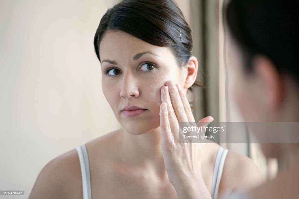 Woman applying face cream : Photo