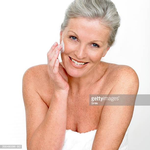 Woman applying face cream smiling, portrait