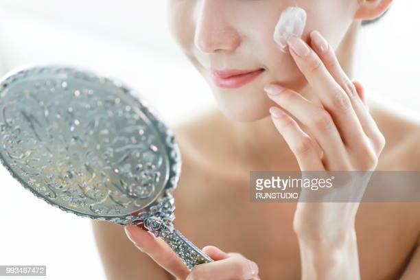 Woman applying face cream with mirror