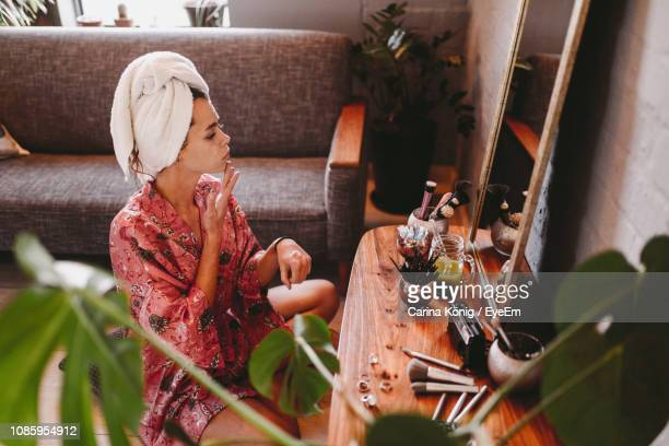 woman applying facial mask while sitting at home - body care and beauty stock pictures, royalty-free photos & images