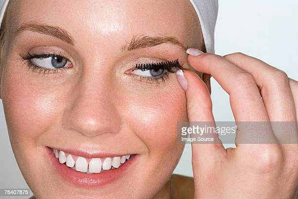 Woman applying false eyelashes
