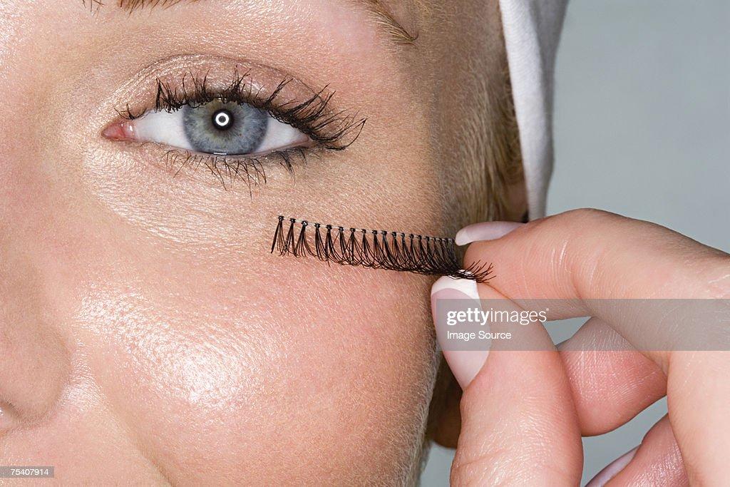 Woman applying false eyelashes : Stock Photo