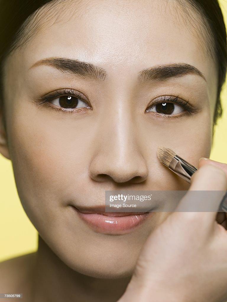 Woman applying foundation : Stock Photo