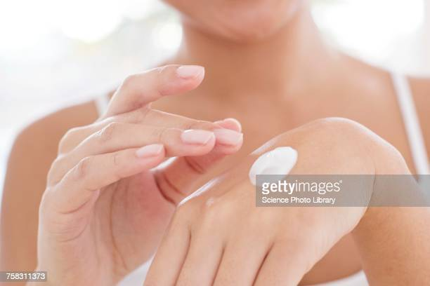 woman applying hand cream - dedo humano imagens e fotografias de stock